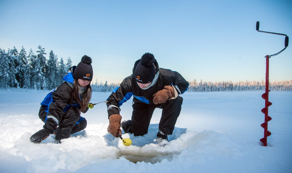 A man and a woman making a hole in the ice