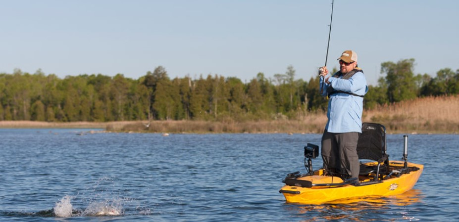 A man fishing from a kayak standing up