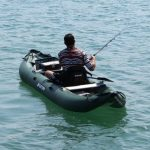 A man with an inflatable fishing kayak on the water